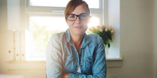Junge Frau im Jeanshemd in sonnigem Büro