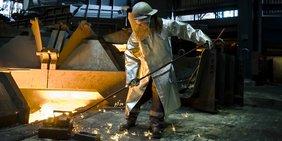 Metallarbeiter iN Schutzkleidung an einer Walzstraße mit glühendem Metall