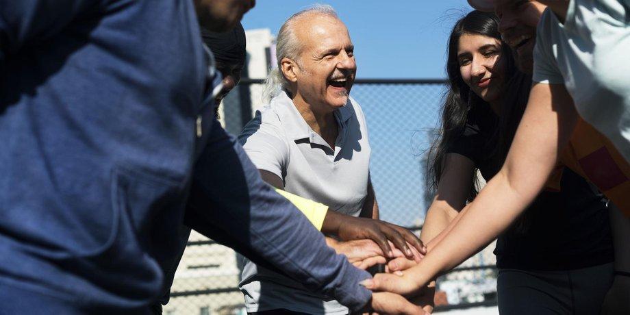 Älterer Mann im Kreis mit jüngeren Mensch die ihre Hände zusammenlegen