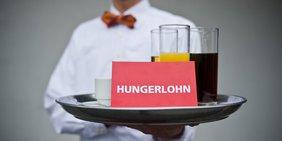 Kellner mit Tablett mit Kleingeld, Getränken und Karte mit der Aufschrift Hungerlohn